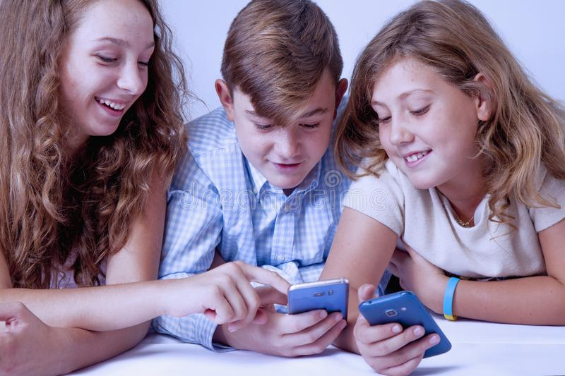 Group of children smiling and gaming on smart phones and mobile stock image