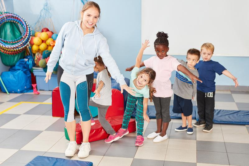 Group of children and sports teacher. Together while doing gymnastics in gym class royalty free stock photography