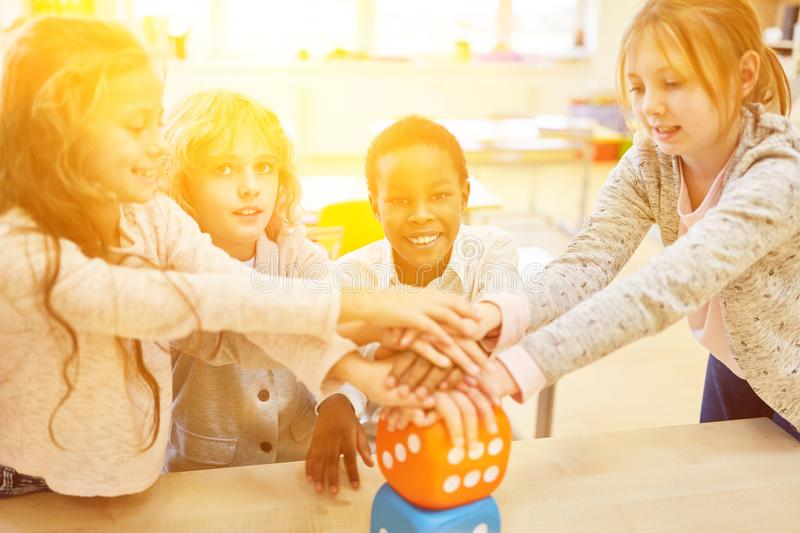Group of children stacks hands as a teamwork concept stock image