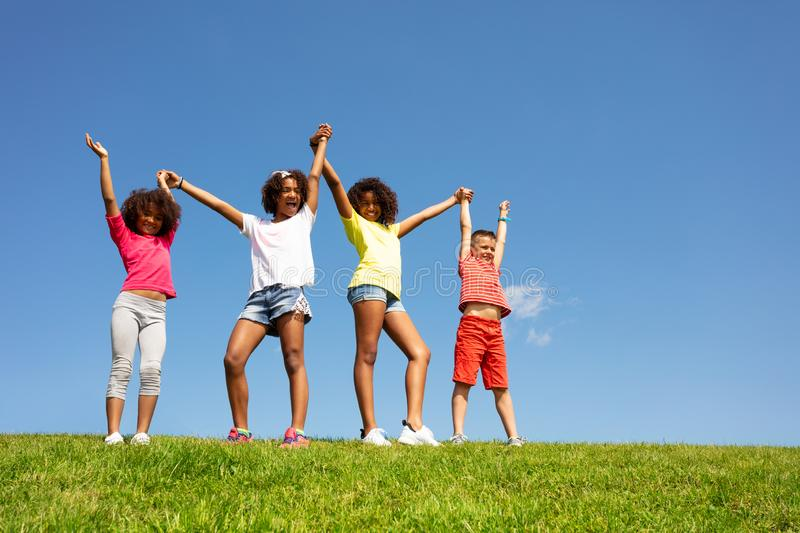 Group of children stand lift hand over clean sky royalty free stock image