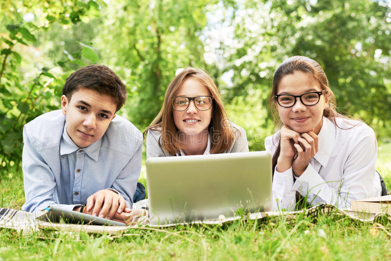 Group of Children Studying on Green Lawn royalty free stock photos