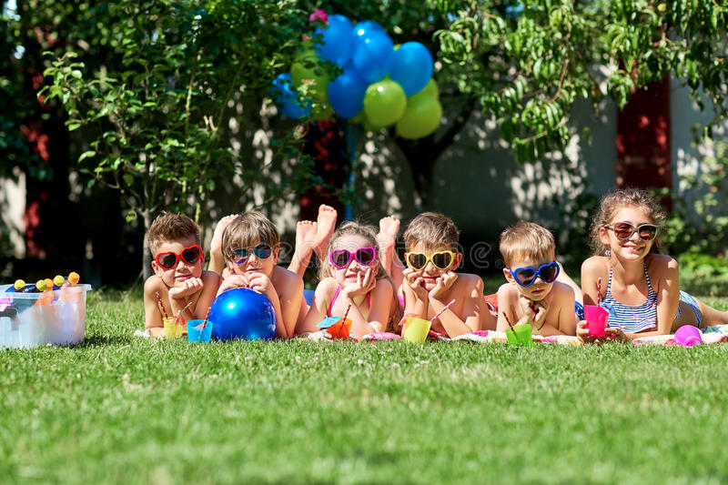 Group of children in sunglasses on grass in summer. royalty free stock photography