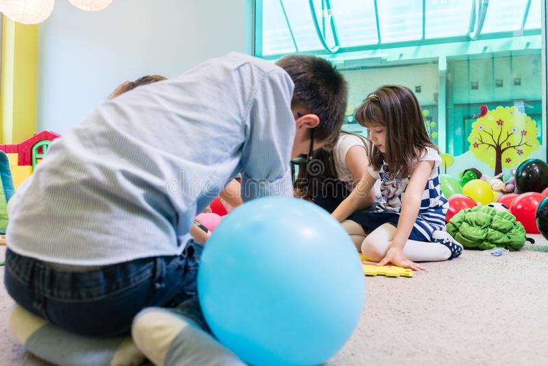 Group of children surrounding their teacher during educational activity. Group of pre-school children surrounding their skilled teacher during an educational royalty free stock photos