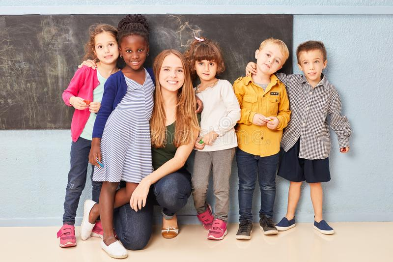 Group of children and teacher as friends royalty free stock image
