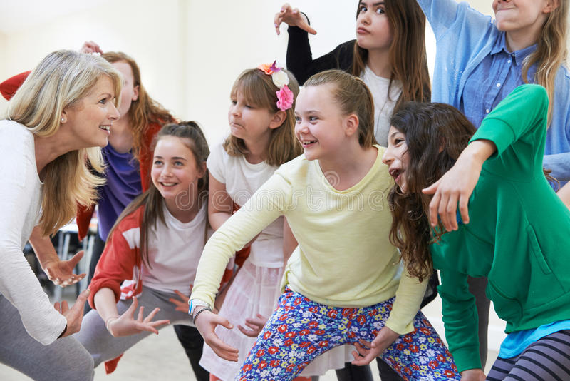 Group Of Children With Teacher Enjoying Drama Class Together. Children With Teacher Enjoying Drama Class Together stock photo