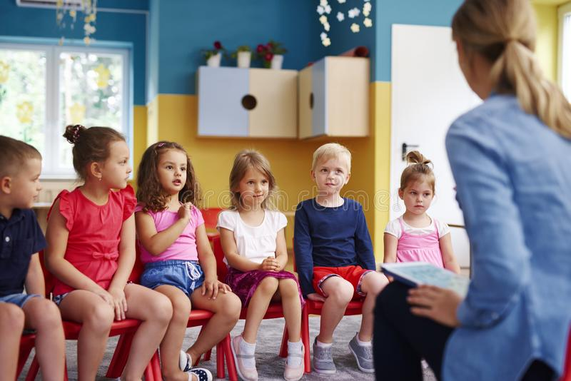 Group of children and teacher in the preschool. Group of children and teacher learning together in the preschool royalty free stock image