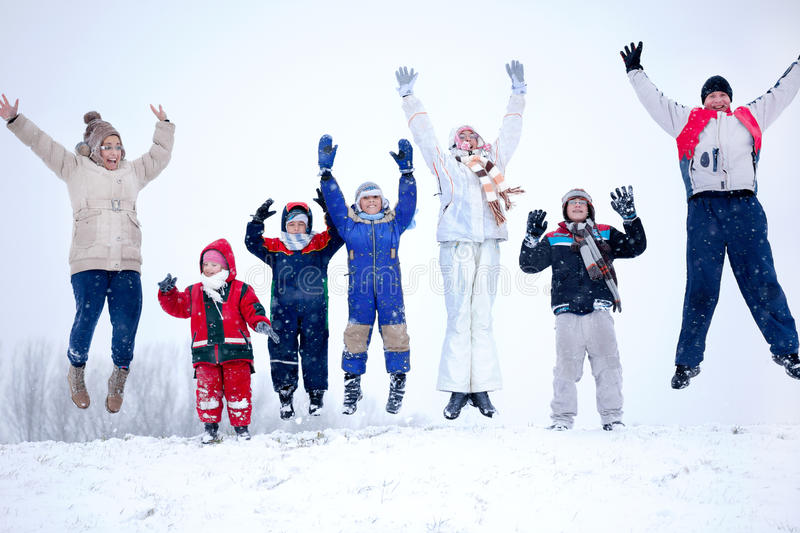 A group of children, women and men jumping in the air at snowy w. Joyful family jumping in the air in the snow royalty free stock photography