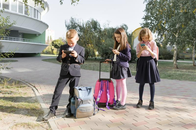 Group of children 7, 8 years old with mobile phones, schoolchildren with backpacks looking into smartphones stock images