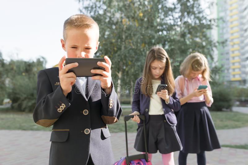 Group of children 7, 8 years old with mobile phones, schoolchildren with backpacks looking into smartphones stock photos