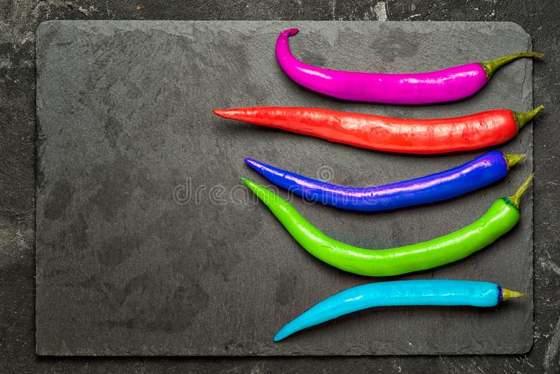 Different and unique concept. Group of chilly peppers with different colors on black stone background , different and unique concept stock photo