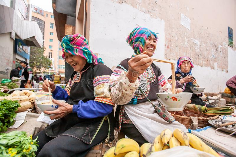 A group of chinese old women vendor wearing traditional costume eating noodle and laughing during sells fresh fruits and vegetable royalty free stock image