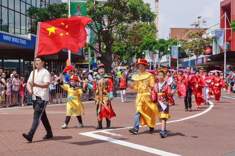 Chinese people in traditional clothing, marching behind Chinese flag royalty free stock photo