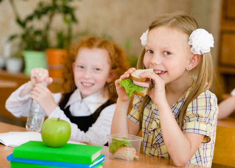 Group of classmates having lunch during break with focus on smiling girl with sandwich royalty free stock image
