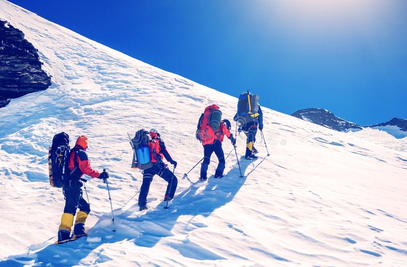 Group of climbers reaches the top of mountain peak. Climbing and stock photography