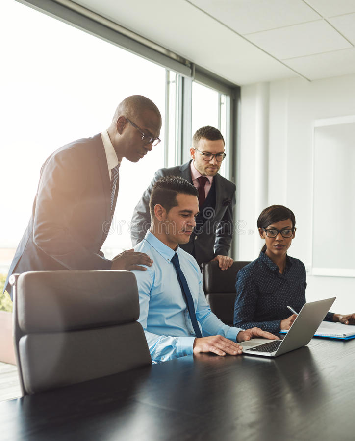 Group of co-workers looking at laptop on table royalty free stock photos