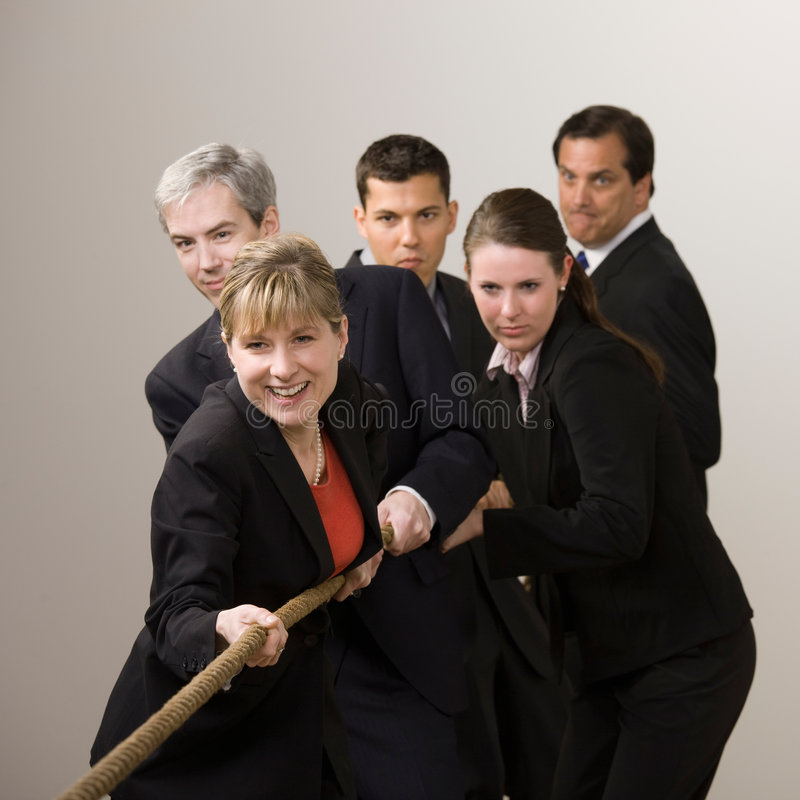 Group of co-workers pulling rope in tug-of-war stock images