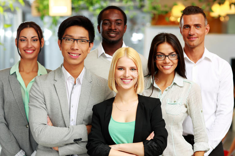 Group of co-workers standing in office. Happy group of co-workers standing in office royalty free stock images