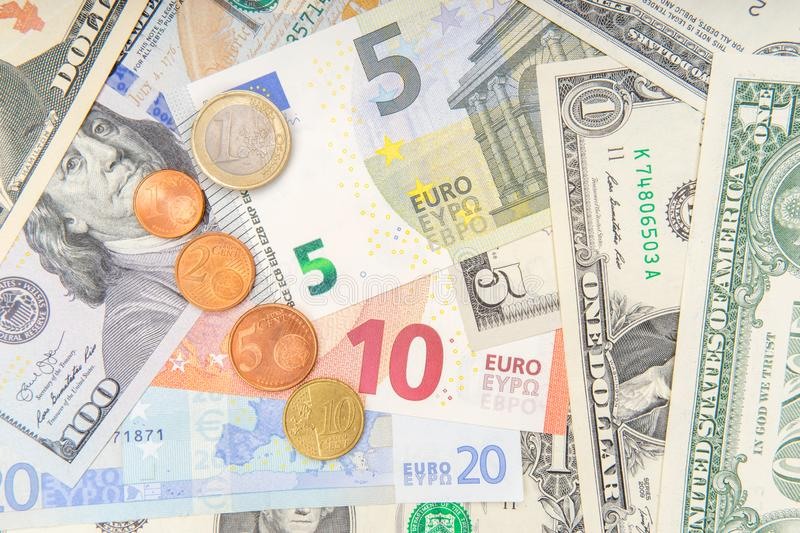 Group of coins on background of various Euro and Dollar banknotes stock photo