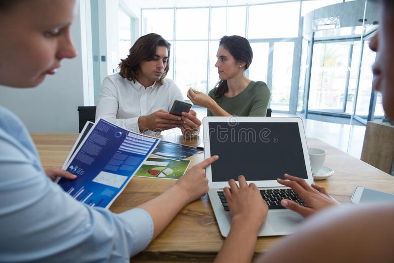 Group of colleague discussing over mobile phone and laptop at desk stock photography