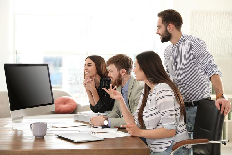 Group of colleagues using video chat on computer in office stock photography