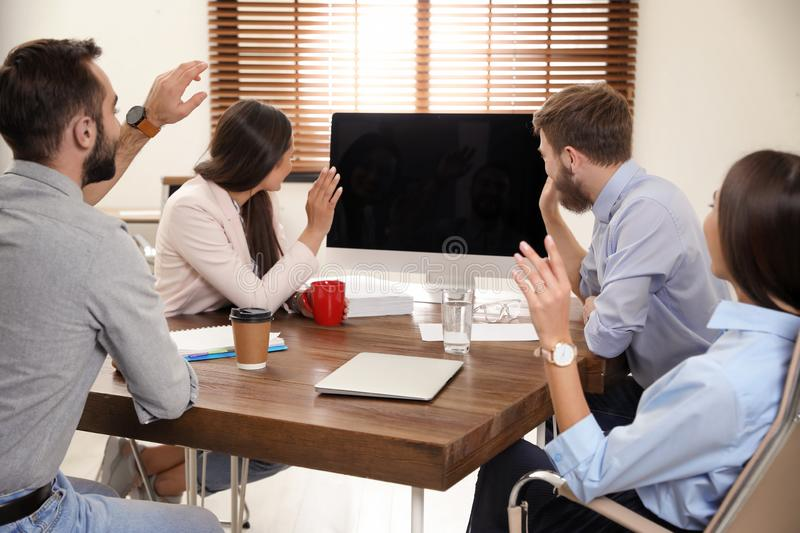 Group of colleagues using video chat on computer in office. Space for text stock image