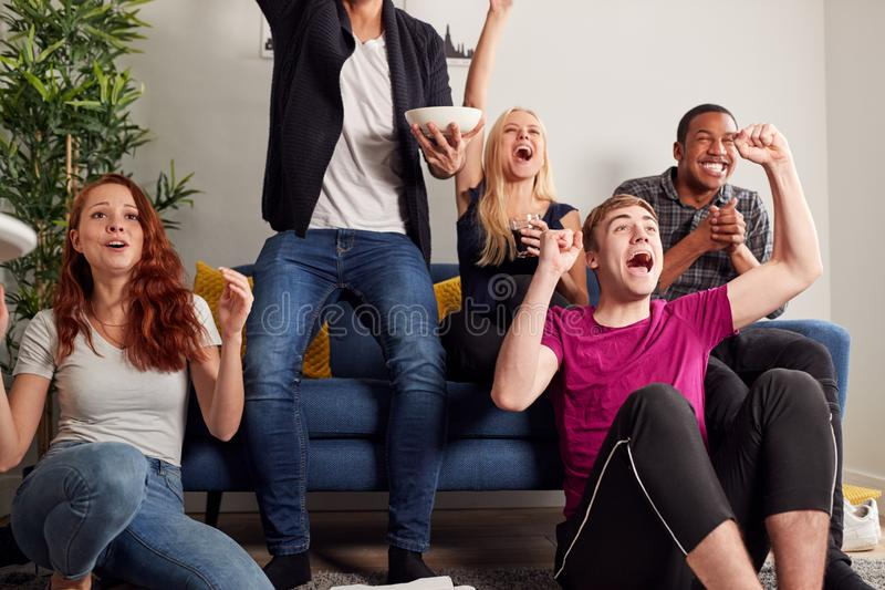Group Of College Friends Celebrating Whilst Watching Sports Game On TV In Shared House royalty free stock photo