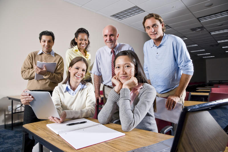 Group of college students and teacher in class. Multiracial group of college students and teacher in class royalty free stock image