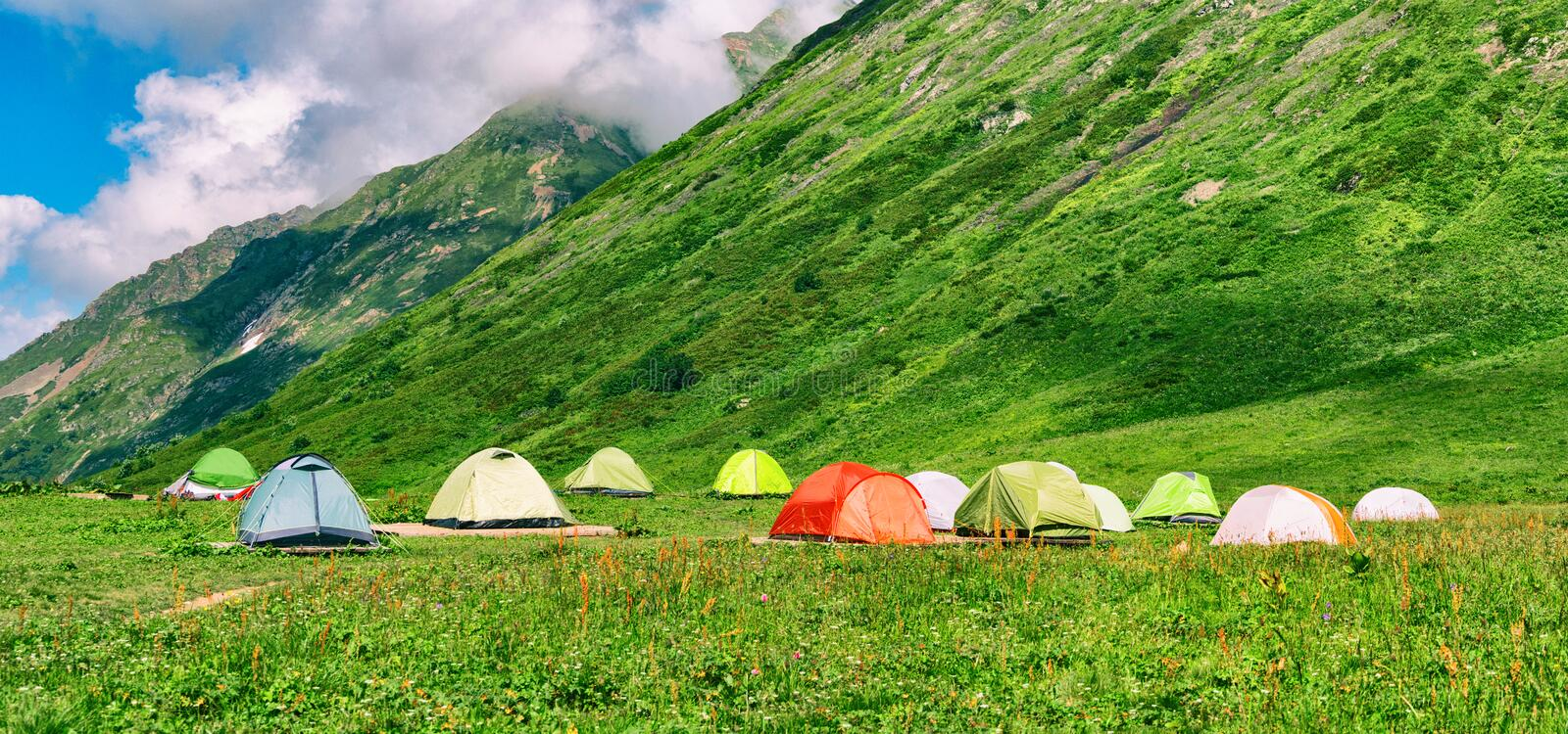 Camping tents in campsite at mountains background royalty free stock photos