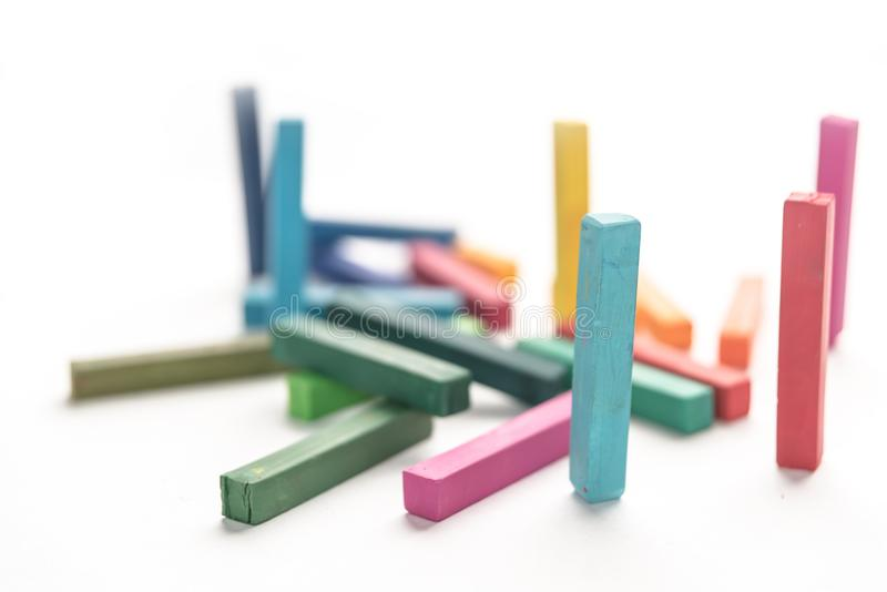 Group colored pastel chalks in a chaotic manner with selective f. Ocus, on white background stock image