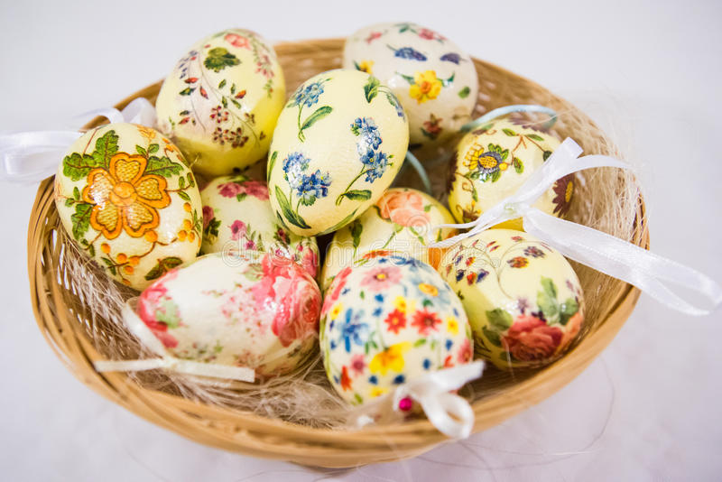 Group of colorful easter eggs decorated with flowers made by decoupage technique, in a basket. On light background royalty free stock images