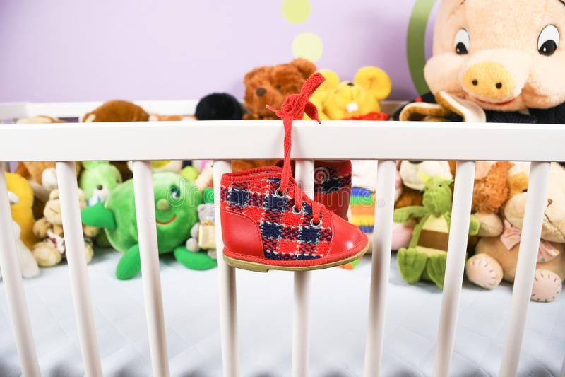 Group of colorful fluffy stuffed animal toys closeup with hanging red small baby shoe. On a white crib fence royalty free stock image