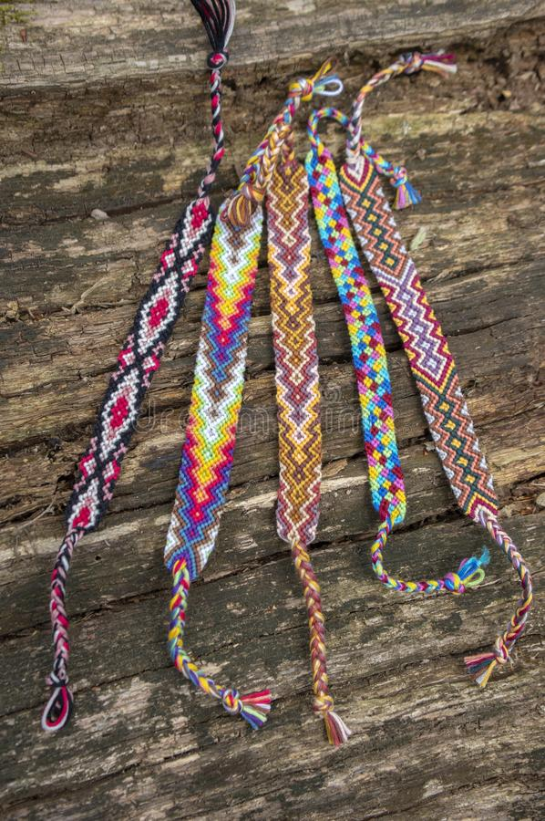 Group of colorful handmade homemade natural woven bracelets of friendship on old wood background, checkered patterns. Group of colorful handmade homemade natural royalty free stock photos
