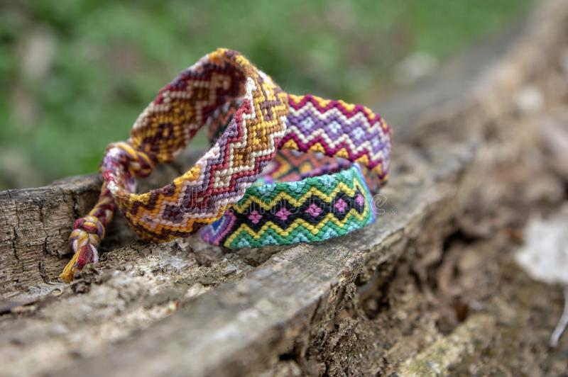 Group of colorful handmade homemade natural woven bracelets of friendship on old wood background, checkered patterns. Group of colorful handmade homemade natural stock photo