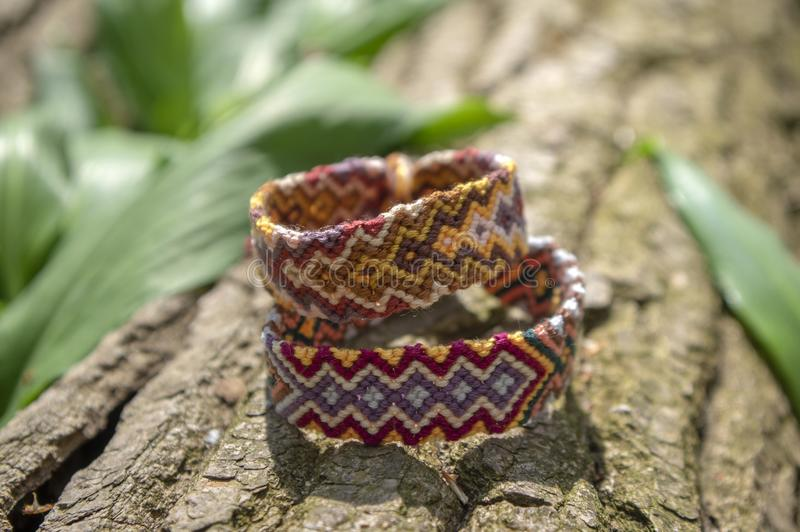 Group of colorful handmade homemade natural woven bracelets of friendship on old wood background, checkered patterns. Group of colorful handmade homemade natural royalty free stock photography