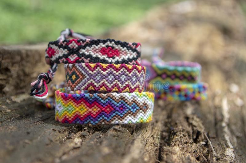 Group of colorful handmade homemade natural woven bracelets of friendship on old wood background, checkered patterns. Group of colorful handmade homemade natural royalty free stock photo