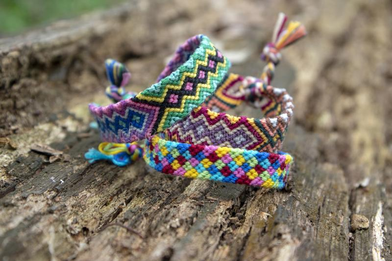 Group of colorful handmade homemade natural woven bracelets of friendship on old wood background, checkered patterns. Group of colorful handmade homemade natural stock image