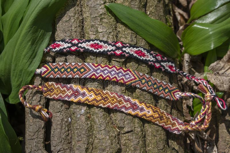 Group of colorful handmade homemade natural woven bracelets of friendship on old wood background, checkered patterns. Group of colorful handmade homemade natural stock images