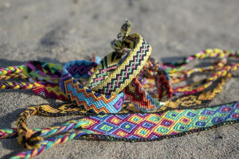 Group of colorful handmade homemade natural woven bracelets of friendship on sand background, rainbow colors, checkered pattern. Bright colors stock image