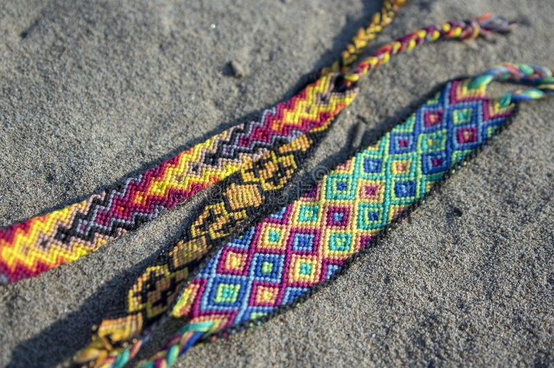Group of colorful handmade homemade natural woven bracelets of friendship on sand background, rainbow colors, checkered pattern. Bright colors stock photo