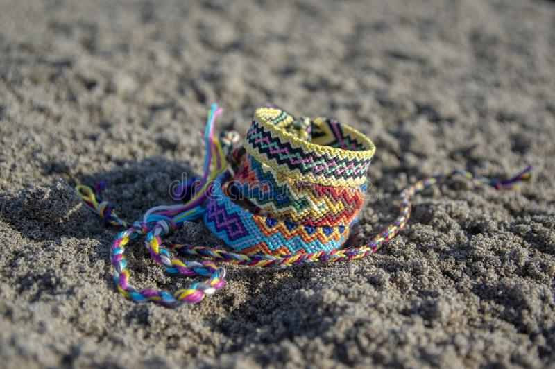 Group of colorful handmade homemade natural woven bracelets of friendship on sand background, rainbow colors, checkered pattern. Bright colors royalty free stock photos