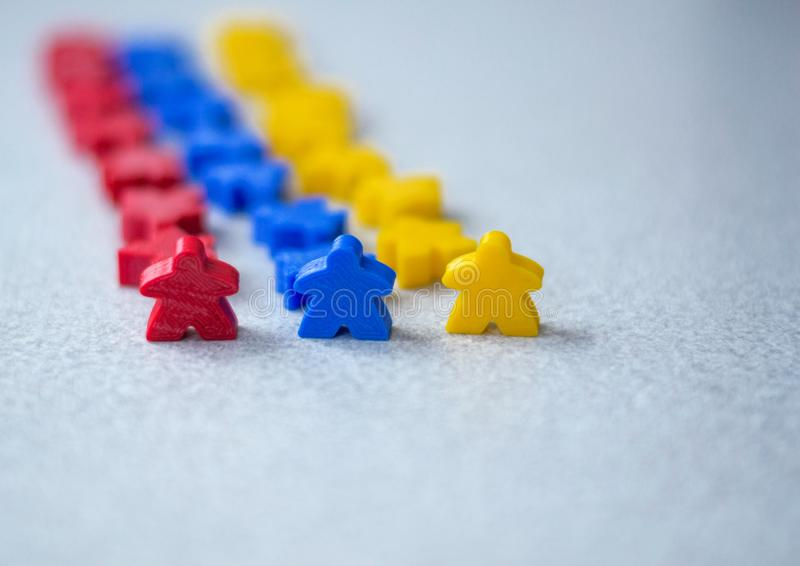 Group of colorful meeples of teams isolated on gray background. Small figures of man. Board games concept. Army and business. stock photography