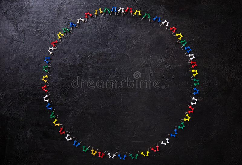 Group of colorful push pins. On black background royalty free stock photo