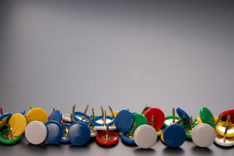 Group of colorful push pins on black board. stock photo