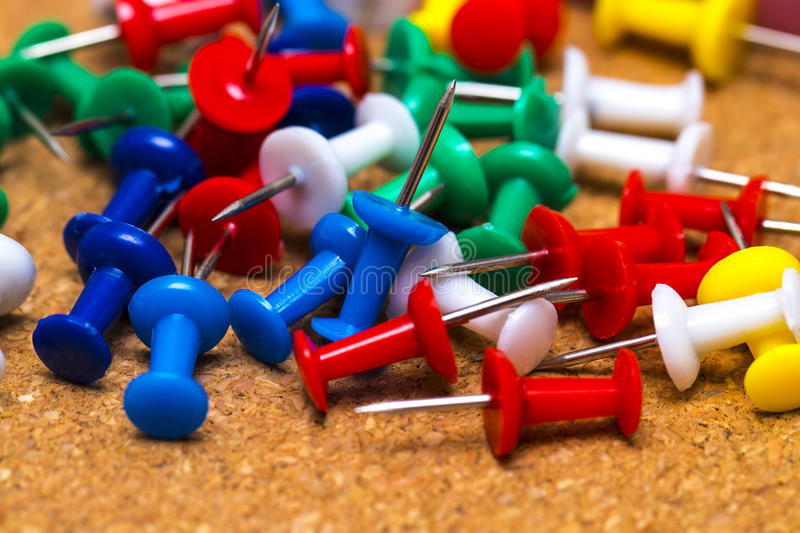Group of colorful push pins on cork board stock images