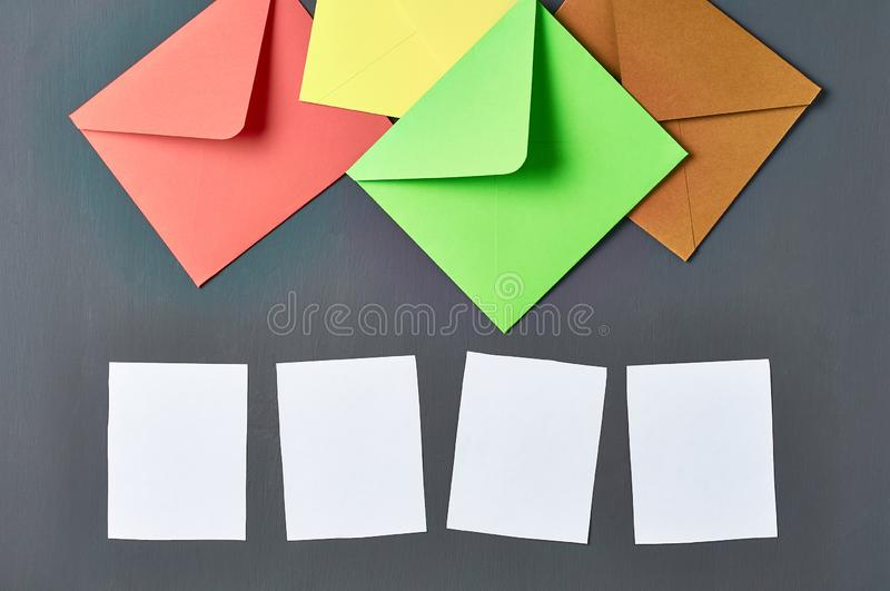 Group of colorful square envelopes near white blank paper sheets lies on old scratched dark concrete. Space for text royalty free stock images