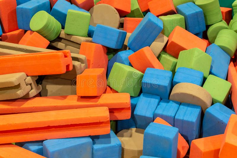 A group of coloured foam blocks in various shapes from cubes, rectangles, cylinders and more creating a colorful background for stock photo