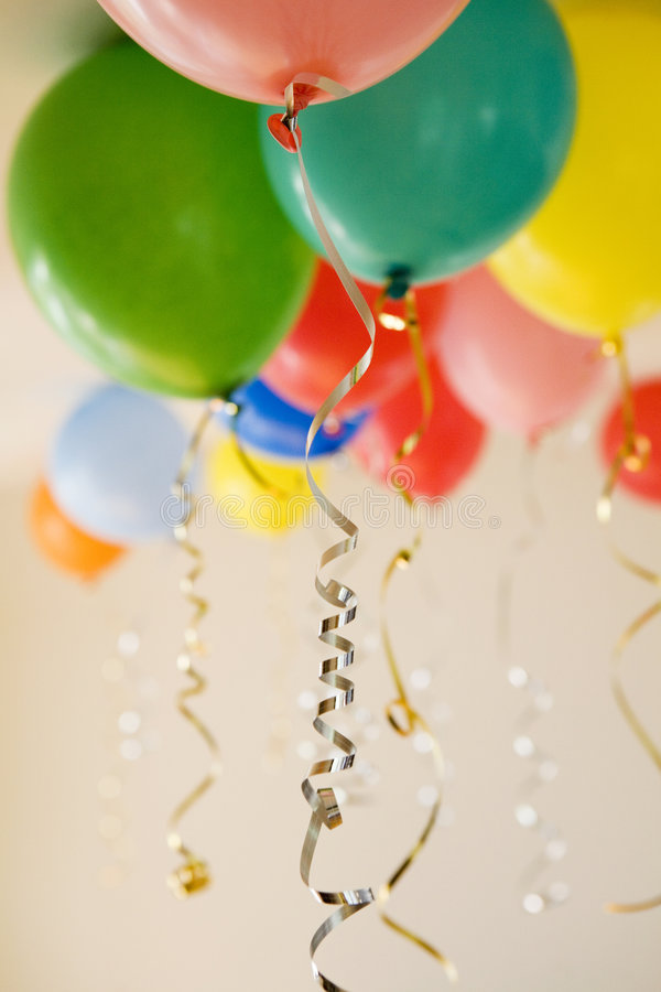 Group of coloured party balloons. With gold and silver strings royalty free stock images