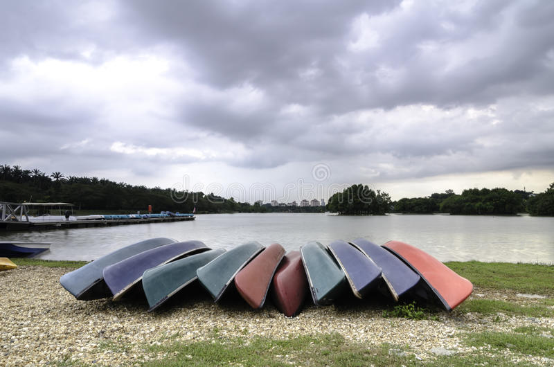 Group of colourful kayaks on the shore of lake stock photos
