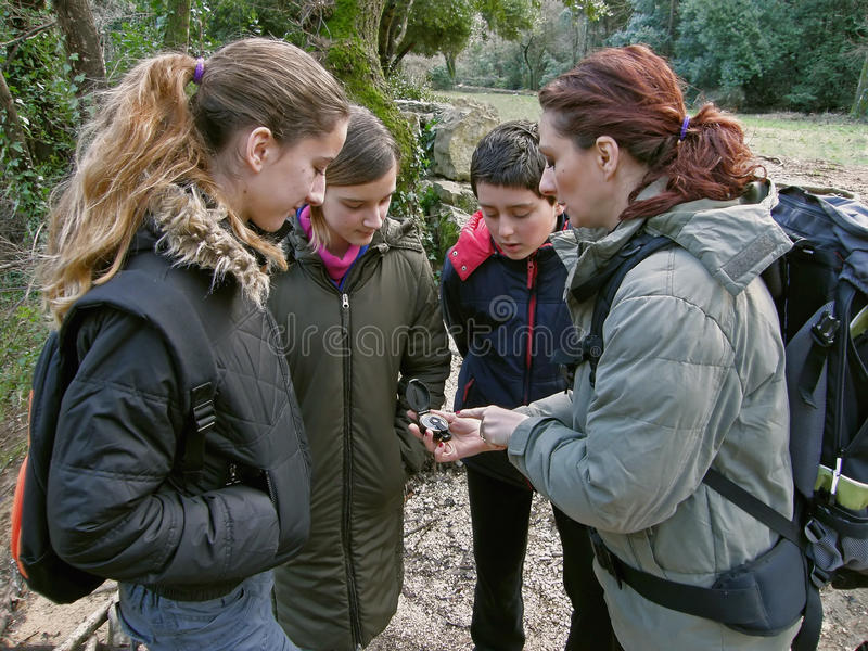 Group with compass in nature. Schools and lecture to students in nature. Woman hold in hand compass and teaches children - teens (best friends) how to orient royalty free stock images
