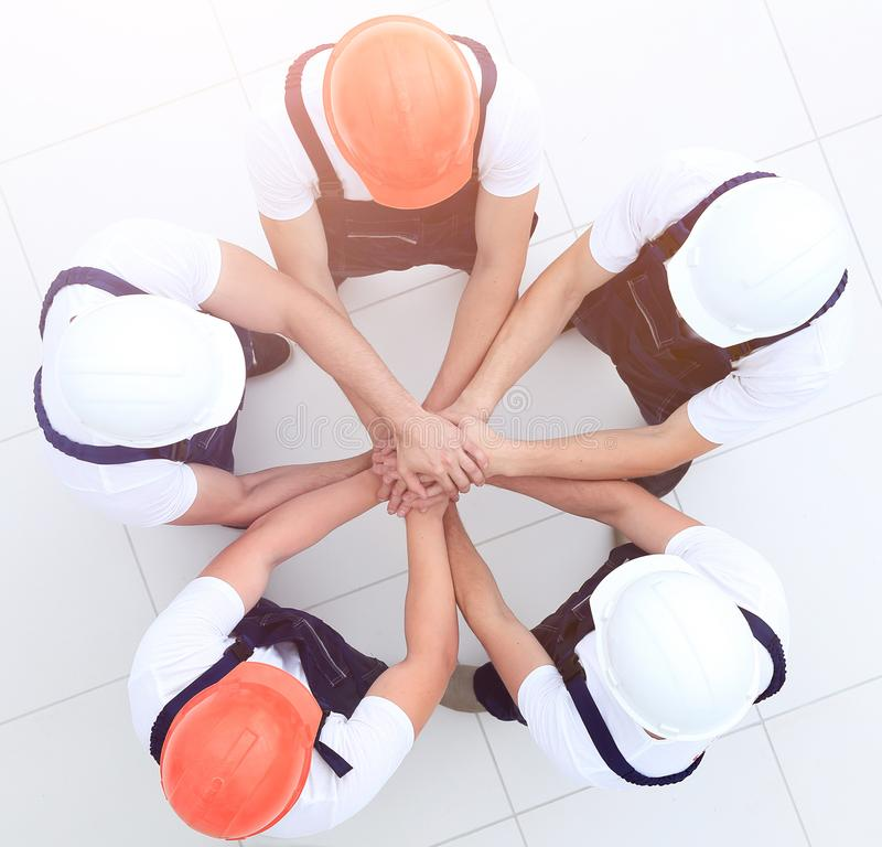 Group of construction workers with hands clasped together. Concept of the team.a close-knit group of builders stock photo